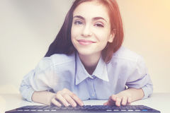 Muchacha sonriente bonita que usa su teclado Fotografía de archivo
