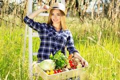 Muchacha sonriente bonita y joven en el sombrero que mantiene la caja de madera llena de verduras Cosecha del verano Foto de archivo