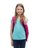 Muchacha sonriente con el bolso de escuela que muestra los pulgares para arriba Foto de archivo libre de regalías