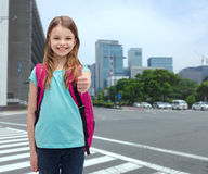 Muchacha sonriente con el bolso de escuela que muestra los pulgares para arriba Foto de archivo