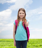 Muchacha sonriente con el bolso de escuela que muestra los pulgares para arriba Imagen de archivo libre de regalías