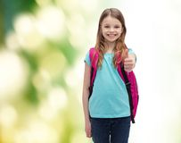 Muchacha sonriente con el bolso de escuela que muestra los pulgares para arriba Imagen de archivo