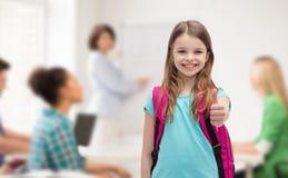 Muchacha sonriente con el bolso de escuela que muestra los pulgares para arriba Fotos de archivo