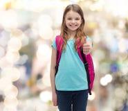 Muchacha sonriente con el bolso de escuela que muestra los pulgares para arriba Fotografía de archivo