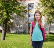 Muchacha sonriente con el bolso de escuela que muestra los pulgares para arriba Fotografía de archivo libre de regalías
