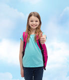 Muchacha sonriente con el bolso de escuela que muestra los pulgares para arriba Imágenes de archivo libres de regalías