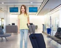 Muchacha sonriente con el bolso del viaje en aeropuerto Fotografía de archivo libre de regalías