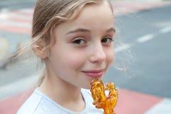Muchacha sonriente con el caramelo ruso tradicional que se coloca en el stre Imagen de archivo