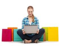 Muchacha sonriente con el comuter y los panieres del ordenador portátil Imagen de archivo libre de regalías