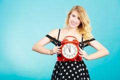 Muchacha sonriente con el despertador en azul Fotos de archivo