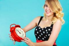 Muchacha sonriente con el despertador en azul Fotografía de archivo libre de regalías