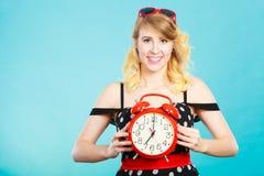 Muchacha sonriente con el despertador en azul Imágenes de archivo libres de regalías