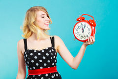 Muchacha sonriente con el despertador en azul Imagenes de archivo