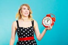 Muchacha sonriente con el despertador en azul Imagen de archivo libre de regalías