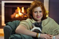 Muchacha sonriente con el gato feliz en casa Foto de archivo libre de regalías