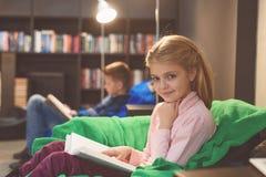 Muchacha sonriente con el libro abierto en sus rodillas Imágenes de archivo libres de regalías