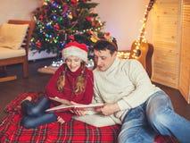 Muchacha sonriente con el libro de lectura del papá cerca del árbol de navidad en casa Fotografía de archivo libre de regalías