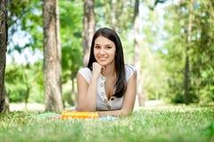 Muchacha sonriente con el libro en parque Fotografía de archivo libre de regalías