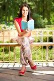 Muchacha sonriente con el libro en parque Foto de archivo