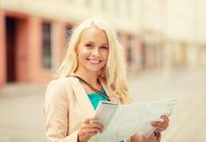 Muchacha sonriente con el mapa turístico en la ciudad Fotos de archivo libres de regalías