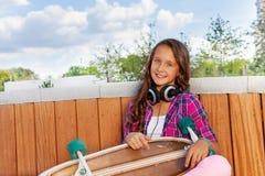 Muchacha sonriente con el monopatín que se sienta en parque Foto de archivo
