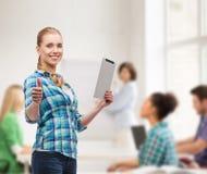 Muchacha sonriente con el ordenador de la PC de la tableta en la sala de clase Foto de archivo