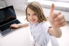 Muchacha sonriente con el ordenador portátil que muestra los pulgares para arriba en casa Imagen de archivo