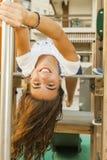Muchacha sonriente con el pelo largo del revés en un oscilación en el parque adentro Imagenes de archivo