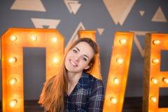 Muchacha sonriente con el pelo marrón largo en una camisa azul en una jaula Fotografía de archivo