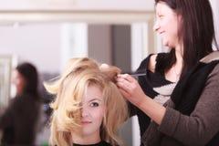 Muchacha sonriente con el pelo ondulado rubio del peluquero en salón de belleza Imagen de archivo libre de regalías