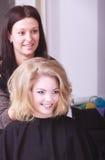 Muchacha sonriente con el pelo ondulado rubio del peluquero en salón de belleza Foto de archivo