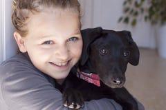 Muchacha sonriente con el perro Fotos de archivo