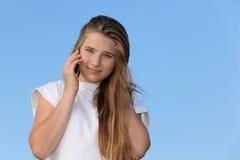 Muchacha sonriente con el soporte del teléfono móvil Imagenes de archivo