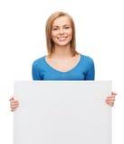 Muchacha sonriente con el tablero blanco en blanco Fotografía de archivo libre de regalías