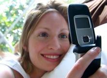 Muchacha sonriente con el teléfono celular móvil Imágenes de archivo libres de regalías