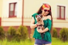 Muchacha sonriente con el terrier del yorkie del perro en las manos Fotos de archivo libres de regalías