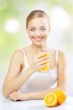 Muchacha sonriente con el zumo de naranja Foto de archivo libre de regalías