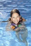 Muchacha sonriente con la bola en la piscina Fotos de archivo