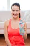 Muchacha sonriente con la botella de agua después de ejercitar Fotos de archivo libres de regalías