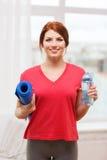 Muchacha sonriente con la botella de agua después de ejercitar Foto de archivo libre de regalías