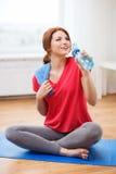 Muchacha sonriente con la botella de agua después de ejercitar Imagen de archivo