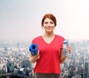 Muchacha sonriente con la botella de agua después de ejercitar Imagenes de archivo