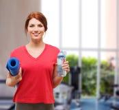 Muchacha sonriente con la botella de agua después de ejercitar Imagen de archivo libre de regalías