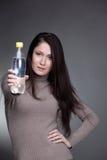 Muchacha sonriente con la botella de agua a disposición Imagenes de archivo