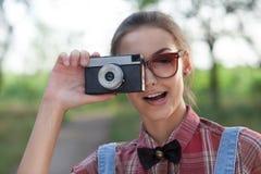 Muchacha sonriente con la cámara retra Imagen de archivo