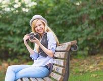 Muchacha sonriente con la cámara retra de la foto que se sienta en banco en el parque Fotos de archivo