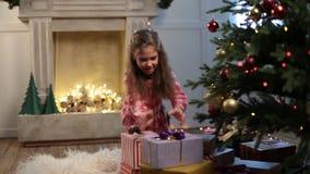 Muchacha sonriente con la caja de regalo de la Navidad en casa almacen de video