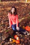 Muchacha sonriente con la calabaza y el maíz en bosque otoñal Imagenes de archivo