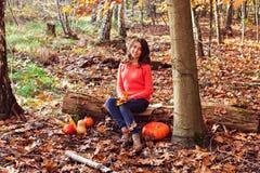 Muchacha sonriente con la calabaza y el maíz en bosque otoñal hermoso Foto de archivo