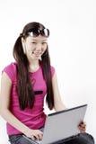 Muchacha sonriente con la computadora portátil Imagen de archivo libre de regalías